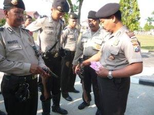 Kasat Samapta AKP Suwardi sedang memeriksa senpi anggotanya beserta kelengkapan surat senpi tersebut